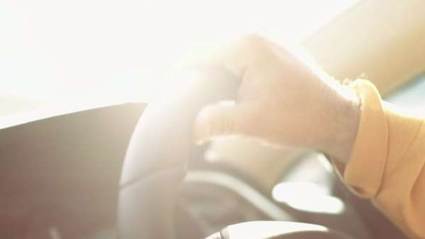 Close-up of adult male hand on steering wheel with sunlight lens flare Royalty-free stock video