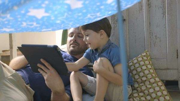 Father using digital tablet with his son under toy tent Royalty-free stock video