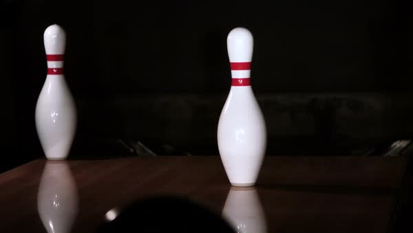 Ultra-slow motion shot of bowling ball knocking down last two pins stock  footage