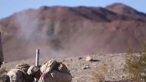 U S  Marines fire mortar rounds in sucession at enemy stock footage