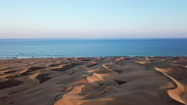 Horizon landscape of beautiful desert with sand dunes, the ocean on the  background and blue sky in sunset light  Wonderful peaceful nature  landscape,