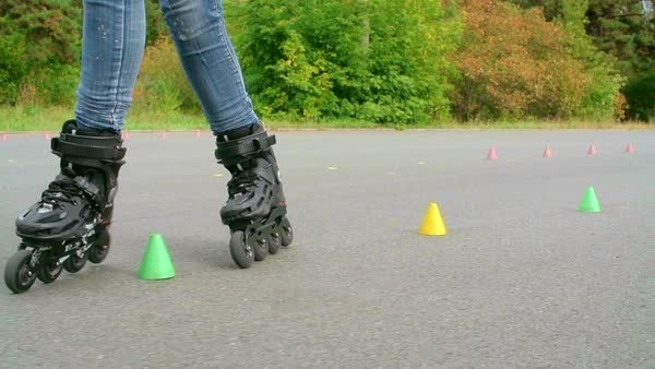 Legs of skilled inline skater doing freestyle activity around the cones Royalty-free stock video