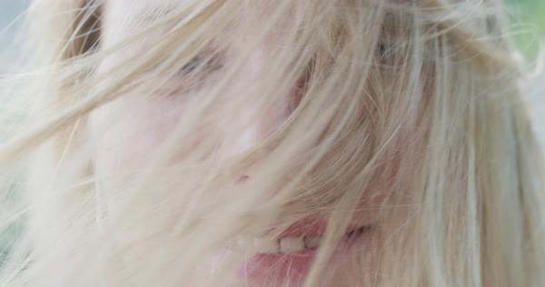 Close-up portrait of beautiful young woman smiling hair blowing in wind outdoors slow motion Royalty-free stock video