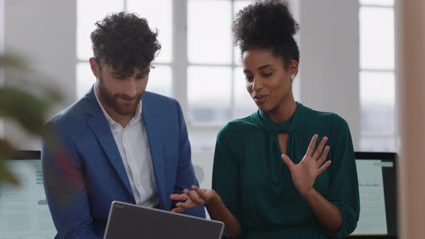 Mixed Race Business Woman Team Leader Brainstorming With Businessman Colleague Using Laptop Computer Showing Ideas Pointing At Screen Working Together