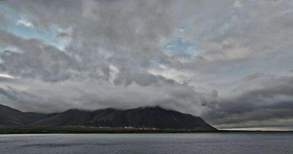 Timelapse of storm clouds rolling over Mountain Range Peaks in Borgarnes, Iceland.  Birds flying over the fjord water. Cars drive past at the mountain base.  Small drops of rain occasionally hit lens and dissolve off. Royalty-free stock video