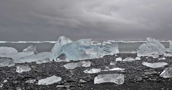 Wide view hyper-lapse of a large iceberg ona black sand beach under a cloudy sky. Jokulsarlon Glacier Lagoon, Iceland Royalty-free stock video