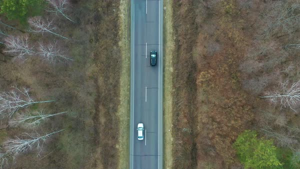 Aerial view of black electric car driving on country road in evening light  stock footage