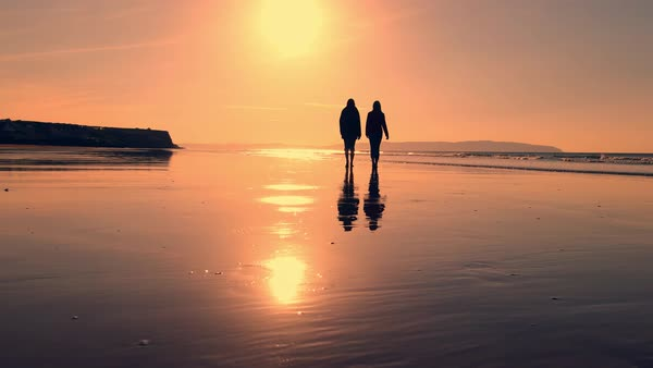 Two people walk on a sandy beach at sunset - Stock Video ...