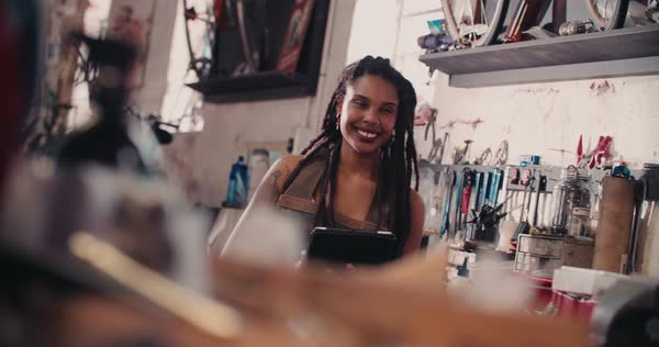 Craftswoman with tattoos and dreadlocks using a digital tablet while standing next to a work bench in a leather apron in a workshop for repairs Royalty-free stock video