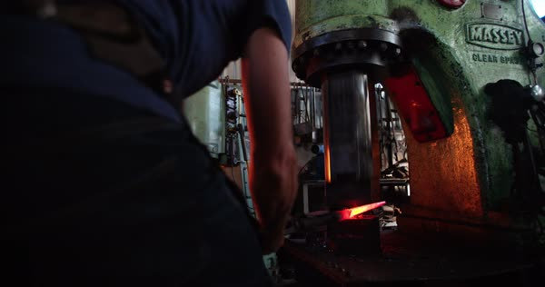 Detail of manufacturing process of wrought iron. Blacksmith holding a piece of iron with tongs while a mechanical press is hammering. Motion blurred effect. Royalty-free stock video