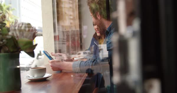 Woman and man sitting at window in coffee shop talking with each other while looking at tablet in hand Royalty-free stock video
