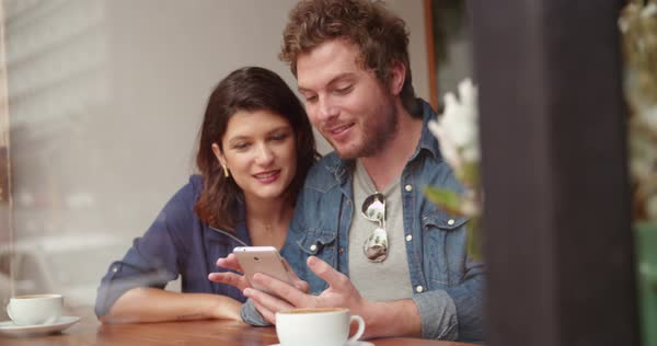 Woman and man sitting at window in coffee shop talking with each other while looking at phone in hand Royalty-free stock video
