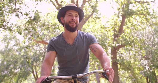 Happy young man laughing and cycling through a sunny park on a summer's day Royalty-free stock video