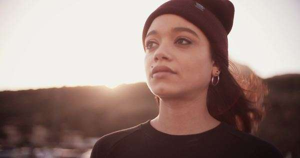 Mixed race grunge girl standing outside with sun flare looking into the distance, slow motion Royalty-free stock video