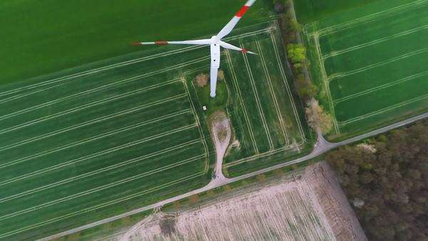 Flying over a wind turbine with rotating blades producing renewable green energy Royalty-free stock video