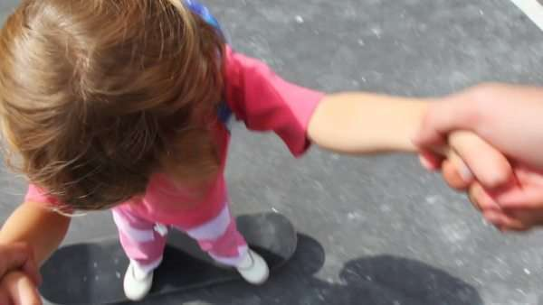 little girl stands on skateboard and it roll on it holding for hands on asphalt Royalty-free stock video
