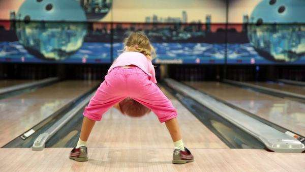 1089db8e4 Little girl in pink clothes throws bowling ball, then jumps and walks away  - Stock Video Footage - Dissolve