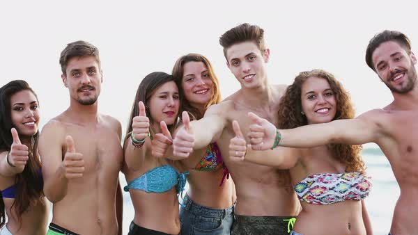 Portrait of friends with thumbs up on beach. Pisa, Tuscany, Italy Royalty-free stock video