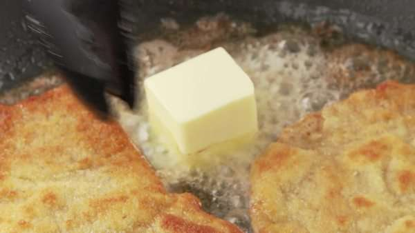 Breaded escalopes being fried in a pan with a knob of butter being added to the pan Royalty-free stock video
