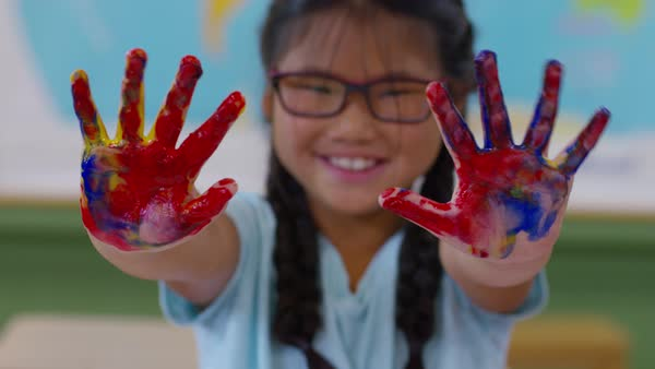 Young Girl Fingerpainting Holds Up Messy Hands Stock Video Footage Dissolve