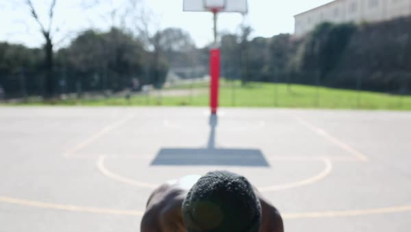 Hans-held shot of a man playing basketball on an empty court Royalty-free stock video