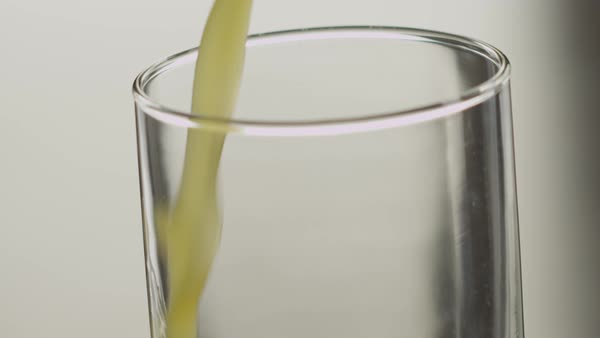 Close-up of orange juice being poured into an empty glass in slow motion Royalty-free stock video
