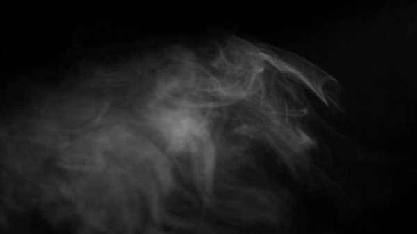 Looping clip of smoky fog rising up into a beam of light against a black background. Royalty-free stock video