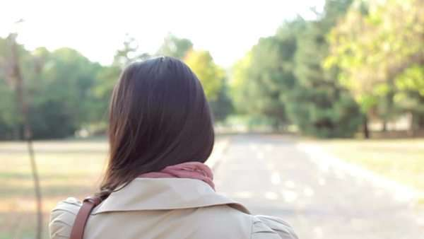 Beautiful Asian woman having a walk on an autumn day, turning back and smiling while looking at the camera. Royalty-free stock video