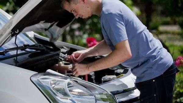 Man replacing car bulb headlights  Young mechanic put out