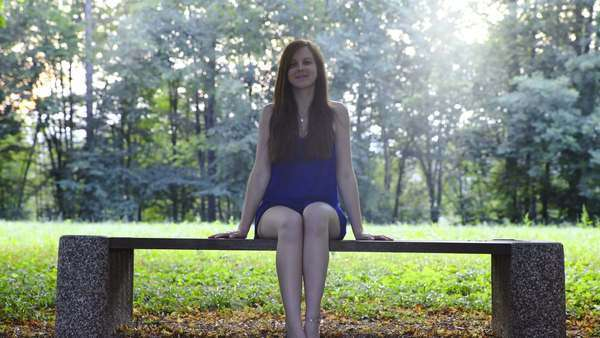 Pretty Girl On Bench Smiling Young Attractive Woman With Brown Long Hair And Blue Dress Sit On Bench In Park With Sun Flares From Background Green