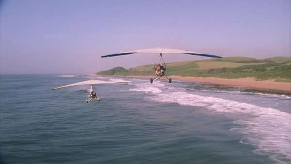 Air to air shot of two microlights flying over the sea Rights-managed stock video