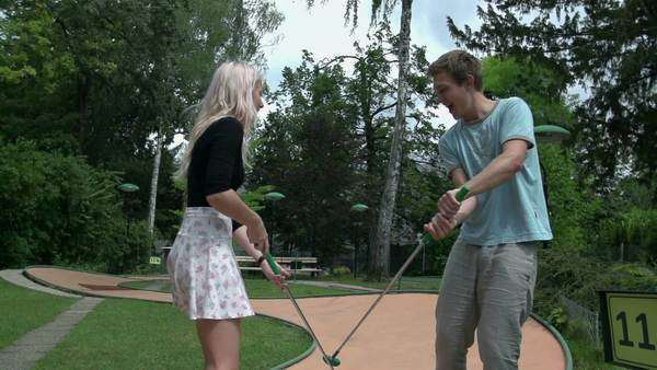 Man and women sword fighting with golf clubs slow motion  Wide shot of  romantic couple playing mini golf and enjoy sword fighting  stock footage
