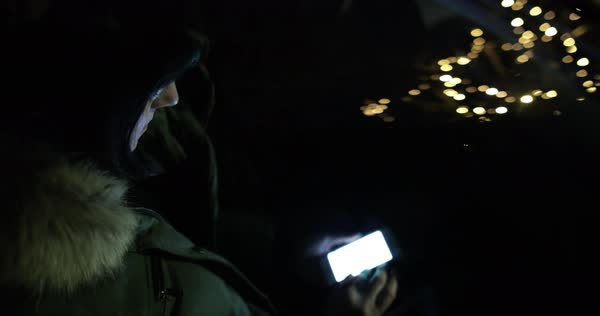 Hand-held shot of a woman using her smartphone at night Royalty-free stock video