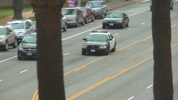 A police car drives on a downtown Los Angeles street by day. Royalty-free stock video