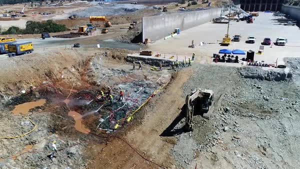 Aerial of workers at the construction site of a new spillway at Oroville  Dam, California  stock footage