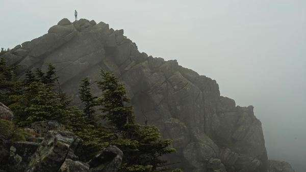 A hiker stands at the top of a large rock face as fog moves through Royalty-free stock video