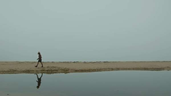 Man walks along water with reflection Royalty-free stock video