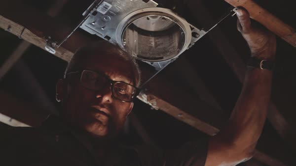 Low-angle shot of a man setting up a lamp in an attic Royalty-free stock video