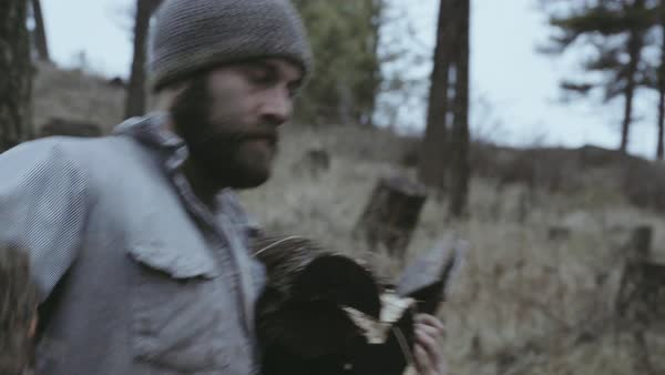 Hand-held shot of a man carrying logs and axes Royalty-free stock video