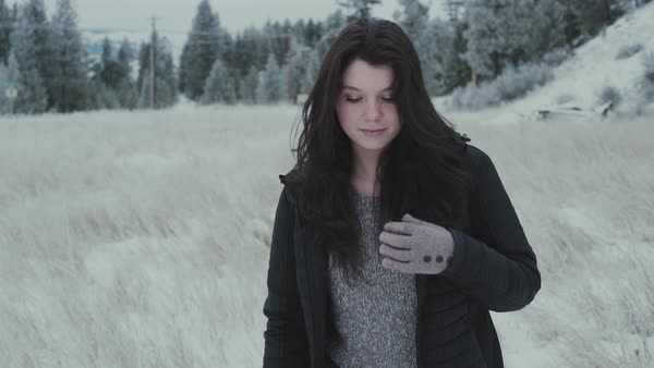 Tracking shot of a young woman walking in a snow covered field Royalty-free stock video