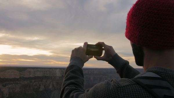 Male wearing beanie takes a photo of the Grand Canyon with his smartphone. Royalty-free stock video
