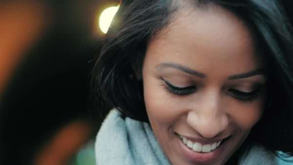 Close-up of attractive young woman smiling at camera and then looking down Royalty-free stock video