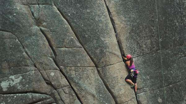 Wide shot of a woman climbing up a cliff Royalty-free stock video