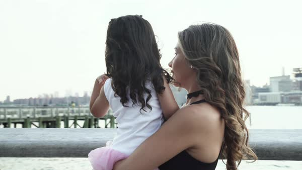Arc shot of a mother holding her daughter along a riverbank Royalty-free stock video