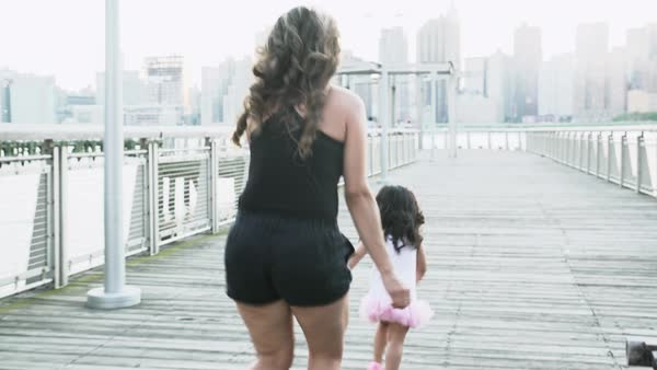 Tracking shot of a young mother running after her daughter on a pier Royalty-free stock video