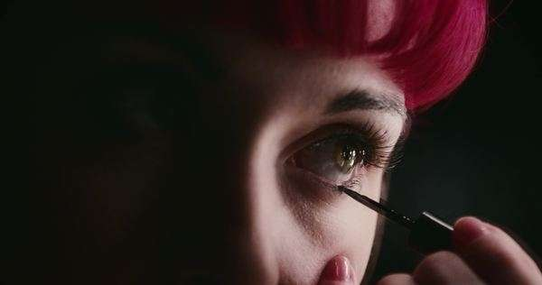 Handheld extreme close up of a young woman applying eyeliner Royalty-free stock video