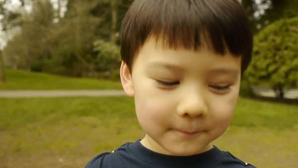 Curious little asian boy places hand over camera lens, takes it away, smiles Royalty-free stock video