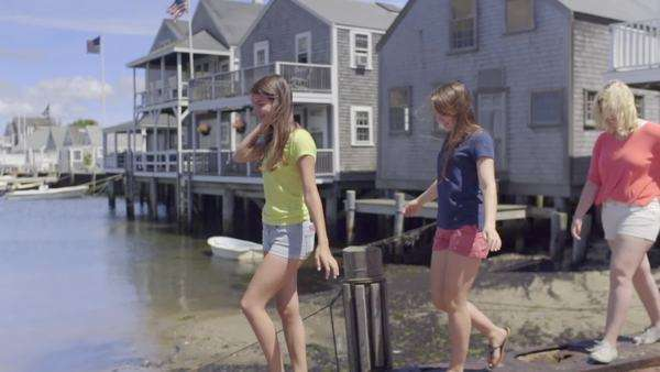 Girls walk single file along sea wall on Nantucket Island, slow motion Royalty-free stock video