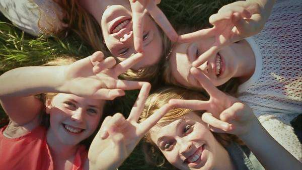 4 sisters lay in grass, they hold their fingers up to create one star Royalty-free stock video