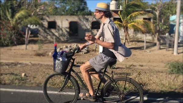 A middle aged man biking on a beach cruiser bicycle holding a glass of wine while riding past an unfinished brick home in Mexico Royalty-free stock video